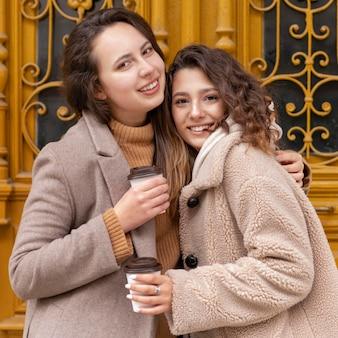 Coup moyen des femmes heureuses avec des tasses à café