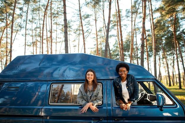 Coup moyen femmes heureuses avec van