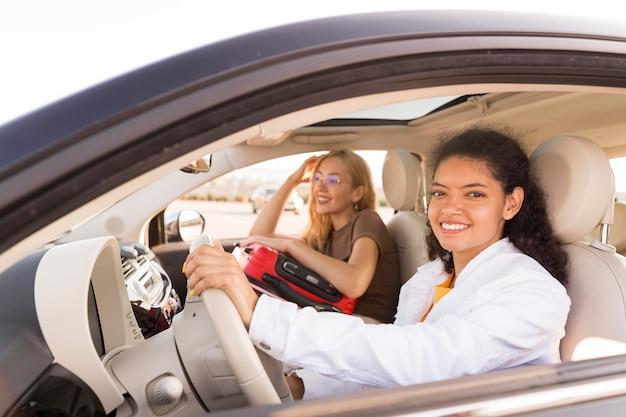 Coup moyen des femmes heureuses voyageant en voiture
