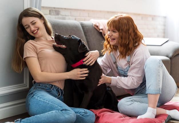 Coup moyen des femmes jouant avec un chien