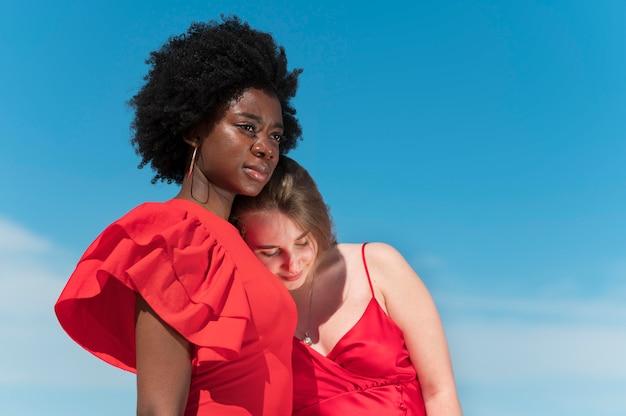 Coup moyen de femmes portant des robes rouges