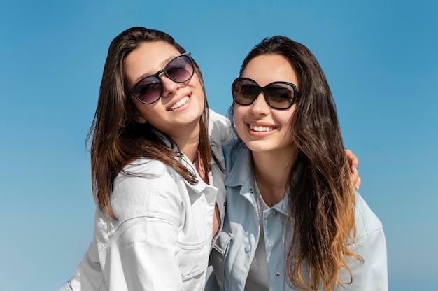 Coup moyen femmes posant avec des lunettes de soleil