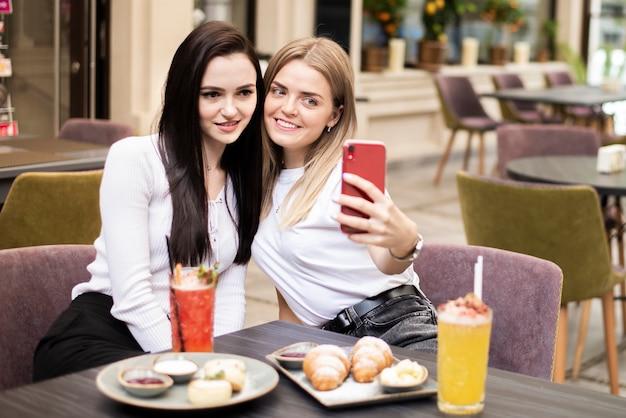 Coup moyen femmes prenant un selfie au restaurant