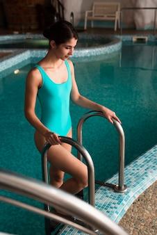 Coup moyen fille brune sortant de la piscine