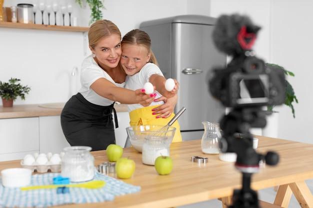 Coup moyen fille et femme tenant des œufs