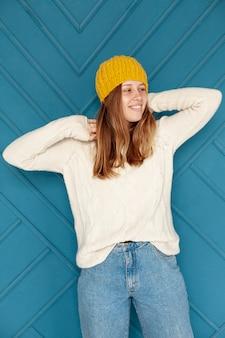 Coup moyen fille heureuse avec chapeau jaune posant