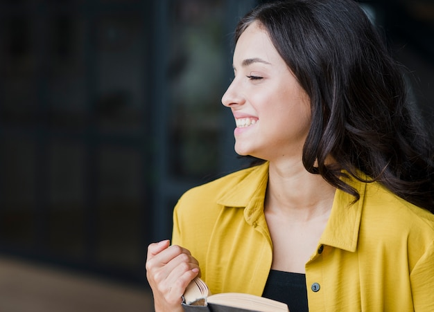 Coup moyen fille heureuse avec livre