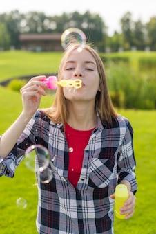 Coup moyen fille jouant avec des bulles de savon