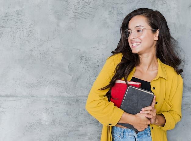 Coup moyen fille avec des livres et fond de ciment