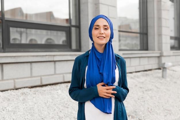 Coup moyen fille magnifique avec hijab souriant à l'extérieur