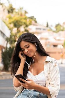 Coup moyen fille portant des écouteurs