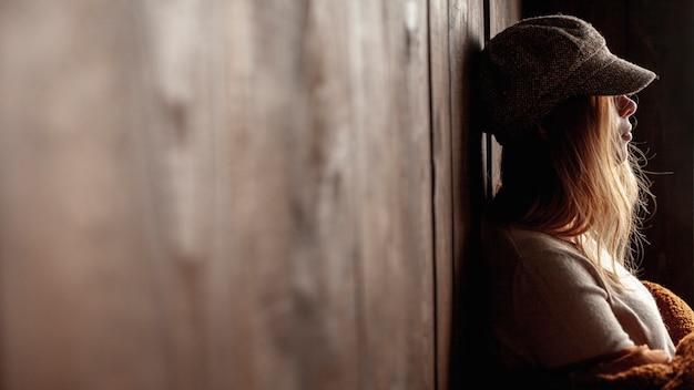 Coup moyen fille posant près d'un mur
