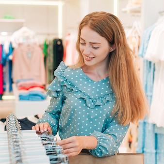 Coup moyen fille vérifiant les vêtements