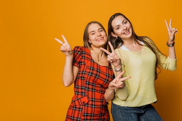 Coup moyen filles heureux faisant signe de la paix