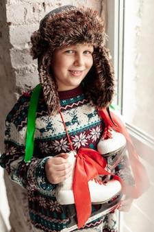 Coup moyen garçon mignon avec chapeau et patins à glace