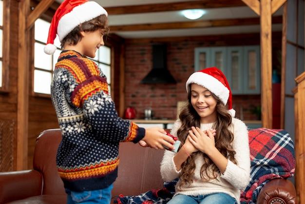 Coup moyen garçon surprenant fille avec cadeau