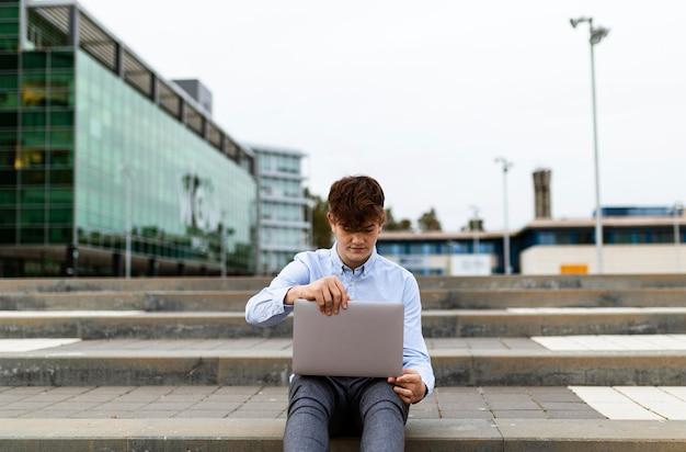 Coup moyen garçon travaillant sur un ordinateur portable à l'extérieur