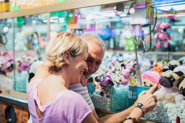 Coup moyen des gens heureux pointant au jouet de chien