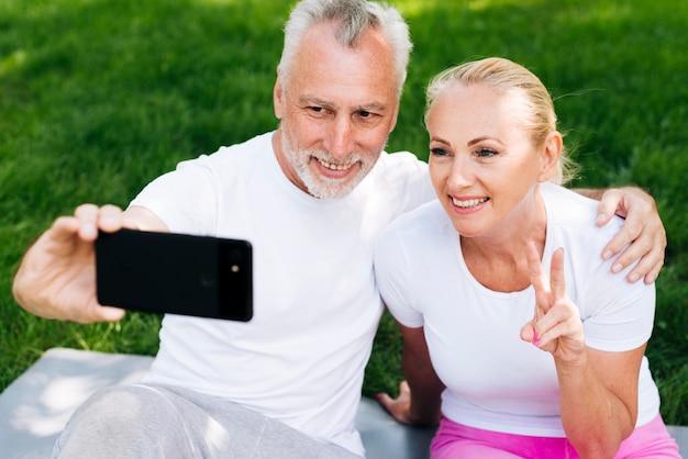 Coup moyen des gens heureux prenant selfies à l'extérieur