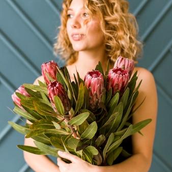 Coup moyen heureuse femme blonde tenant un bouquet