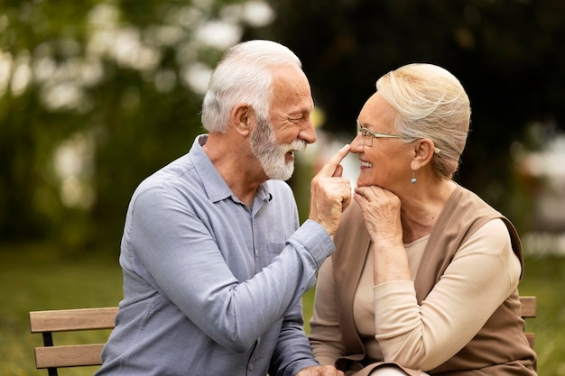 Coup moyen heureux couple de personnes âgées à l'extérieur
