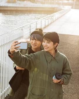 Coup moyen heureux couple prenant selfie