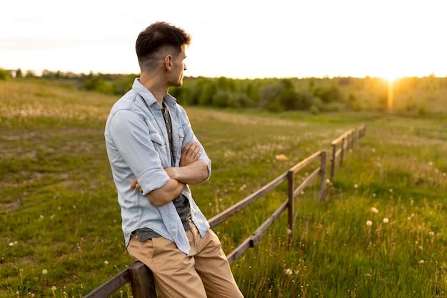 Coup moyen homme assis sur une clôture