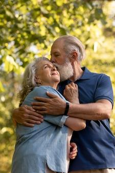 Coup moyen homme embrassant une femme sur la joue