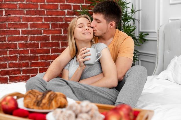 Coup moyen homme embrassant une femme avec une tasse