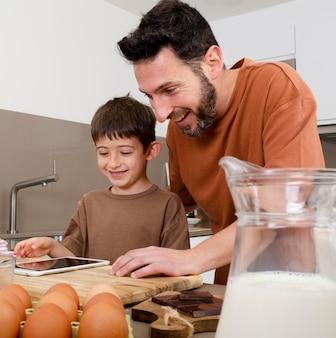 Coup moyen homme et enfant dans la cuisine