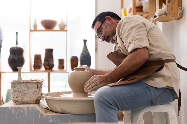 Coup moyen homme faisant de la poterie à l'intérieur