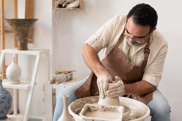 Coup moyen homme faisant de la poterie