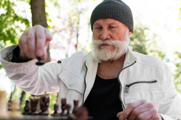 Coup moyen homme jouant aux échecs à l'extérieur