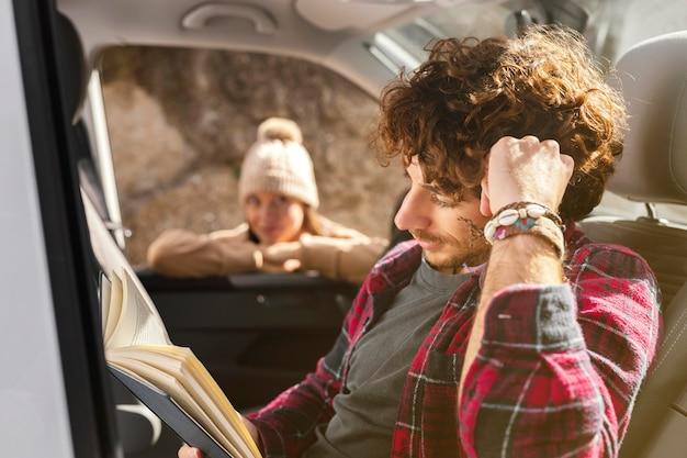 Coup moyen homme lisant dans la voiture