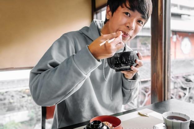 Coup moyen homme mangeant avec des baguettes