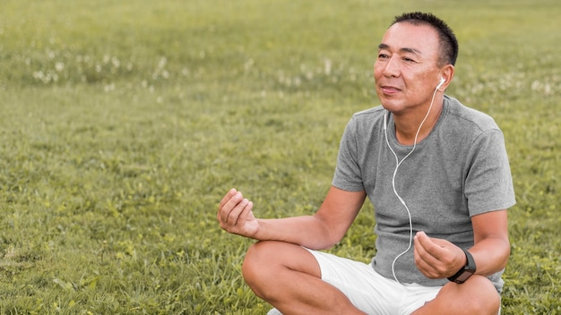 Coup moyen homme méditant sur l'herbe