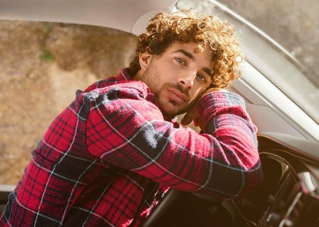 Coup moyen homme posant dans la voiture