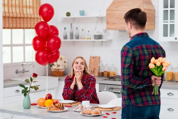 Coup moyen homme surprenant femme avec des fleurs