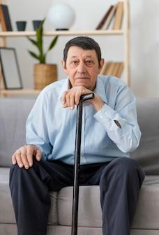 Coup moyen homme tenant un bâton de marche