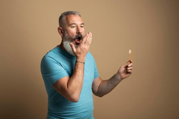 Coup moyen homme tenant une brosse à dents