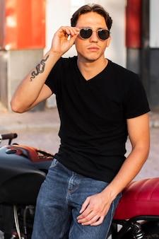 Coup moyen homme tenant des lunettes de soleil