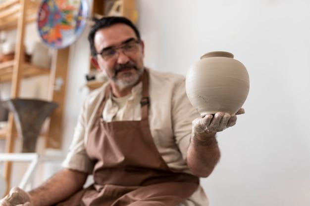 Coup moyen homme tenant un pot