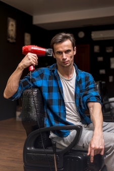Coup moyen homme tenant un sèche-cheveux