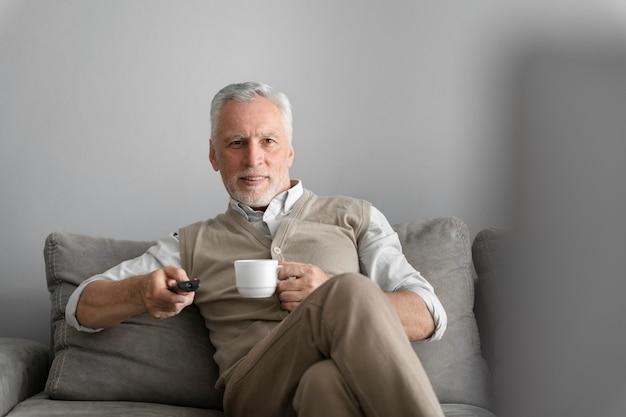 Coup moyen homme tenant une tasse sur un canapé