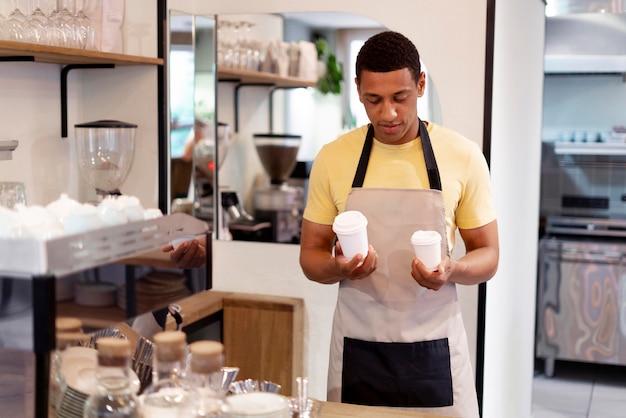 Coup moyen homme tenant des tasses à café