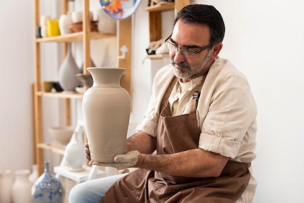 Coup moyen homme tenant un vase