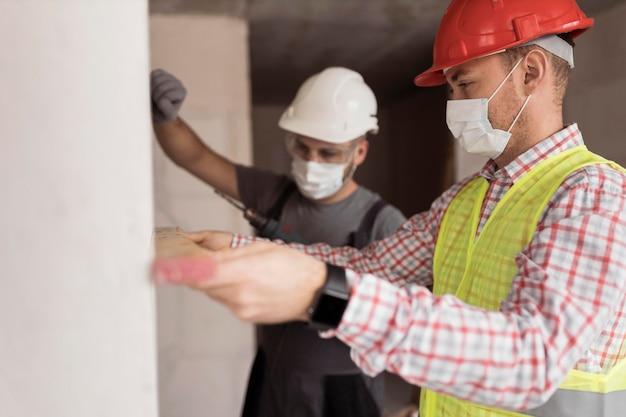 Coup moyen des hommes travaillant avec des masques