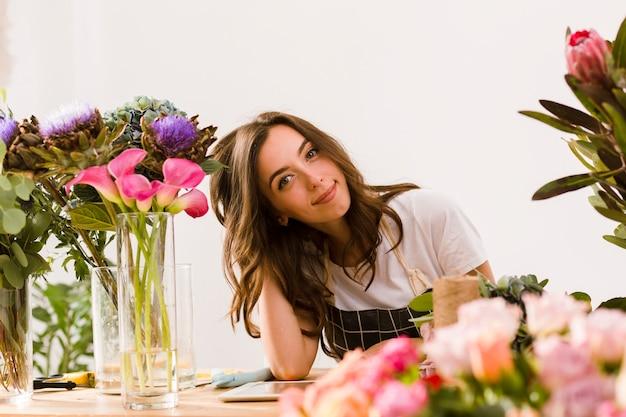 Coup moyen jeune fleuriste au magasin de fleurs