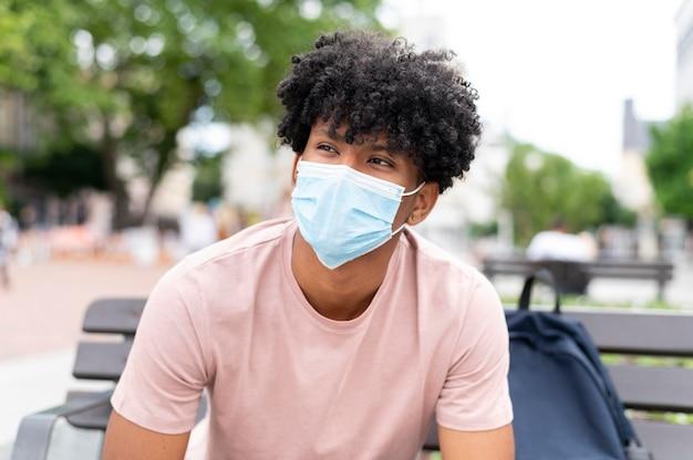Coup moyen jeune homme portant un masque à l'extérieur