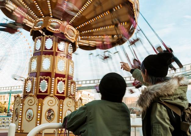 Coup moyen joli couple pointant sur le carrousel